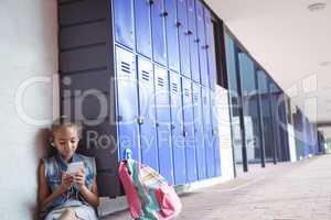 Elementary schoolgirl listening music through headphones while using mobile phone