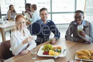 Portrait of smiling business colleagues sitting at breakfast table