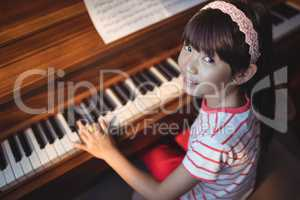 High angle portrait of girl practicing piano in classroom