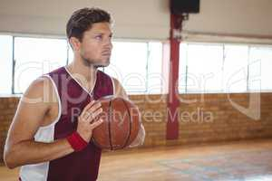 Man practicing basketball in court