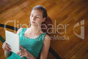 Female basketball player using digital tablet while relaxing in court