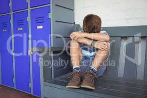 Full length of boy sitting on bench by lockers