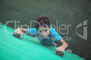 Portrait of boy climbing green wall