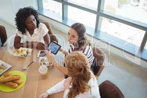 Female business colleagues discussing over digital tablet around breakfast table
