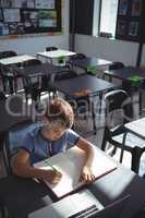 High angle view of boy writing in book at desk