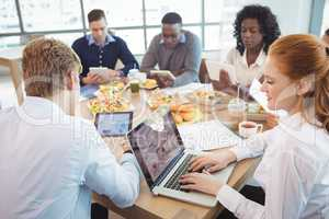 Business colleagues using laptop and digital tablets around breakfast table
