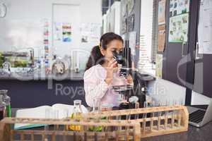 Elementary schoolgirl looking through microscope at laboratory