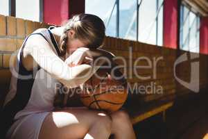 Tired basketball player sitting by window