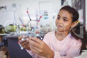 Elementary student examining molecule model