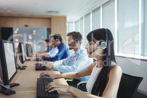 Businesswoman typing on keyboard at call center