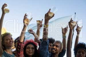 Happy friends holding beer glasses while enjoying music festival