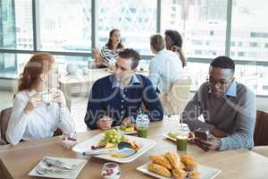 Business entrepreneurs sitting at breakfast table in office