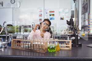 Elementary schoolgirl holding test tube at laboratory