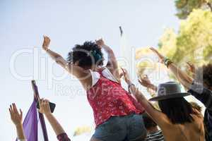 Tilt image of friends enjoying against sky at music festival