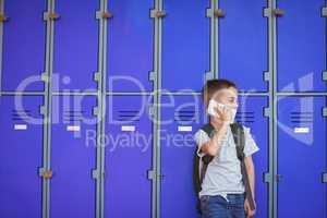 Elementary boy talking on mobile phone against lockers