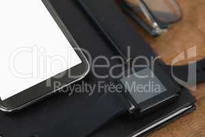 diary, smart watch, pencil, smartphone and spectacles on wooden background