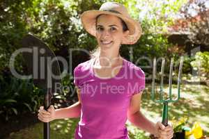 Portrait of smiling beautiful woman holding gardening fork and shovel