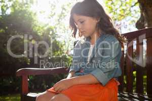 Sad girl sitting on wooden bench against plants