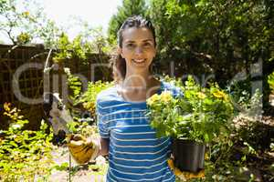 Portrait of smiling beautiful woman holding trowel and potted plant on sunny day