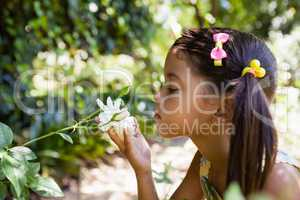 Side view of girl smelling white flower