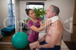 Young female therapist examining neck collar on senior male patient