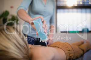 Midsection of female therapist pouring ultrasound gel on boy