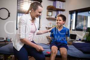 Smiling female therapist looking at boy while hitting at knee with reflex hammer