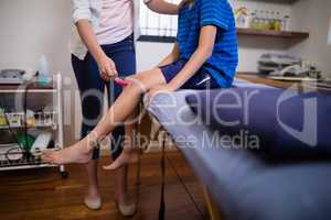 Low section of young female therapist hitting boy with reflex hammer on knee