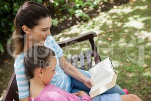 Tilt shot of mother reading novel to daughter on wooden bench