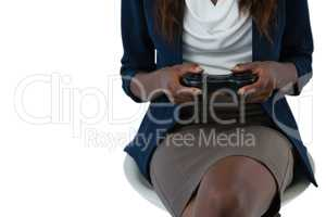 Mid section of businesswoman playing video game