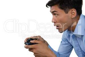 Side view of young businessman making face while playing video game