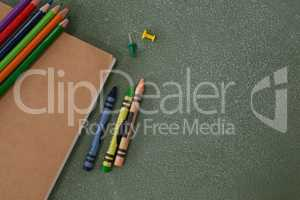 Color pencils, crayons, push pins and book on chalkboard