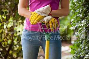 Midsection of woman holding gardening fork standing amidst plants