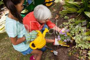 High angle view of girl standing with watering can by grandmother planting