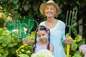 Portrait of smiling girl standing with grandmother holding gardening equipment