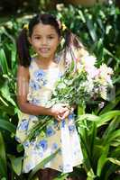 Portrait of smiling girl holding flowers bouquet standing amidst plants