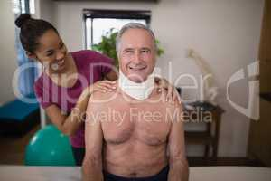 Smiling female therapist looking at senior male patient with neck collar