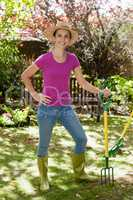 Portrait of smiling beautiful woman holding gardening fork
