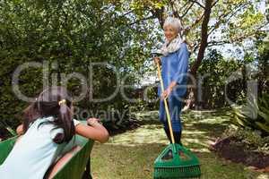 Senior woman holding rake while looking girl sitting in wheelbarrow