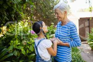 Smiling senior woman holding hands of granddaughter while standing against plants