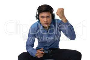 Businessman with fist wearing headphones while playing video game