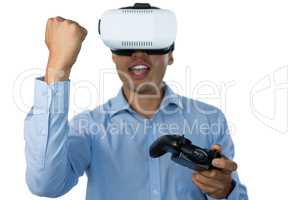Businessman with vr glasses clenching fist while playing video game