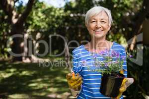 Portrait of senior woman holding potted plant and trowel