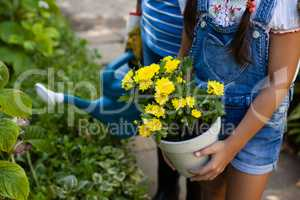 Midsection of senior woman and granddaughter holding watering can and yellow flower pot