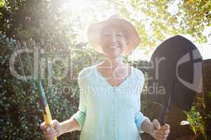 Back lit portrait of smiling senior woman holding garden fork and shovel
