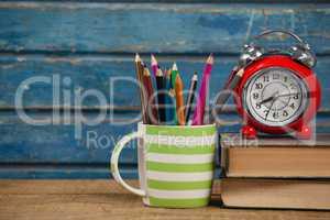 Alarm clock, books and pen holder