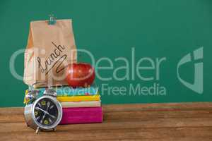 Alarm clock, lunch paper bag and apple on books stack