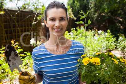 Portrait of smiling beautiful woman holding trowel and flowering pot
