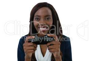 Close up of smiling businesswoman playing video game