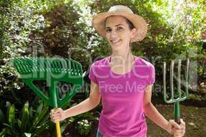 Portrait of smiling beautiful woman holding gardening fork and rake